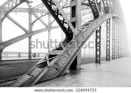 Black and white photo of a steel bridge over a river in fog, Cracow, Poland