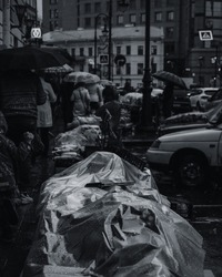 Black and white photo of a street market under the rain. People under the umbrellas in the background. Street photography concept, wet goods on market.