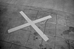 Black and white photo of a street parking spot marked with a large X sign