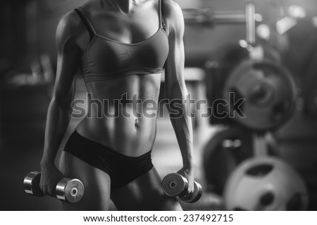 Black and white photo of a strong fitness woman. Brunette sexy fitness girl in sport wear with perfect body in the gym posing before training set. Fitness woman in the gym. Fitness woman with dumbbell