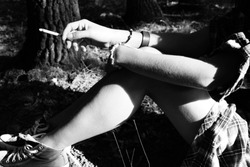 Black and white photo of a woman holding a cigarette/smoking sitting down in a forest/trees Lost in the woods, stressed,anxiety