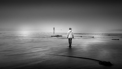 Black and White Photo of a Woman walking in Dense Fog on the Sandy Beach in Cox Bay at the Pacific Rim National Park on Vancouver Island, British Columbia, Canada