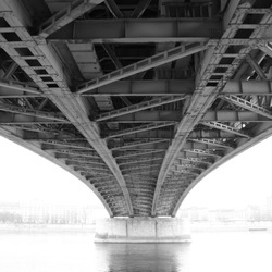 black and white photo of an abstract steel construction from under the bridge