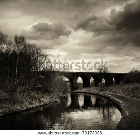 Black and white photo of an arc bridge with dramatic sky in Huddersfield. #73173358