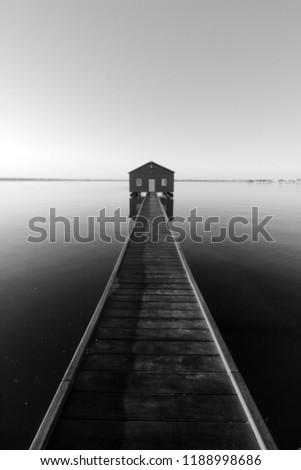 Black and white photo of an old boat shed at the end of a jetty or pier.