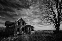 Black and white photo of an old scary abandoned farm house that is deteriorating with time with an old tree and a hangman's noose topped off with a dark sky.