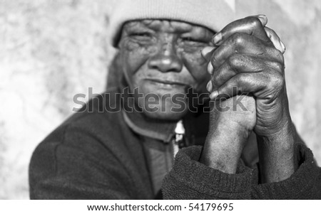 Black and white photo of an senior african woman with folded hands - focus on the weathered hands