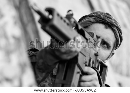 Shutterstock Black and white photo of armed & dangerous soldier shooting with automatic rifle.Terrorist military man in combat ammunition targeting with rifle gun.Guerrilla soldier ready to fight.Armed forces team