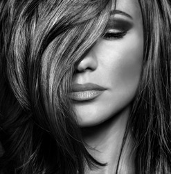 Black and white photo of attractive supermodel with sexy stylish makeup and healthy shiny hair, seductive female on luxury photo shoot