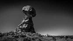 Black and White Photo of Balanced Rock, a tall and delicate sandstone Rock Formation in the desert landscape of Arches National Park near Moab in Utah, United States