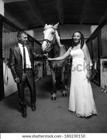 Black and white photo of bride and groom holding horse by rein at stable