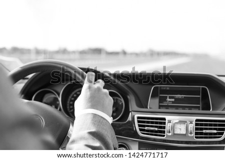 Black and White photo of Cropped image of businessman in formals driving car #1424771717