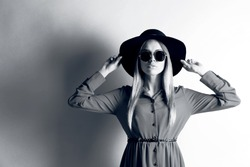 Black and white photo of expressive young model with hat and sunglasses