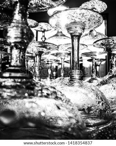 Black and White photo of freshly washed Marie Antoinette champagne glasses, stacked and glistening in the sun.