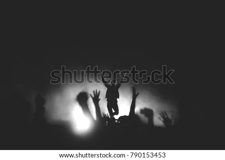 Black and white photo of frontman in a stage backlights with hands raised up to the crowd #790153453
