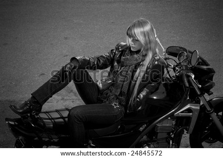Black and white photo of girl sitting on a motorbike.