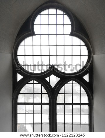 Black and white photo of gothic latticed window in stone wall. Close-up of medieval architecture detail in backlight.
