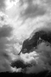 Black and white photo of hight Alps mountains and white clody sky with sunlight