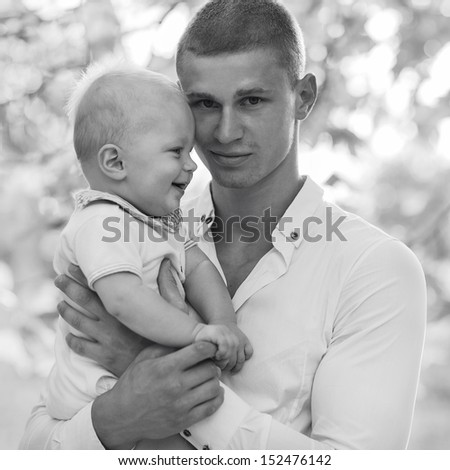 Black and white photo of his father and a small child. Father looks into the camera. The son looks at his father and laughs.
