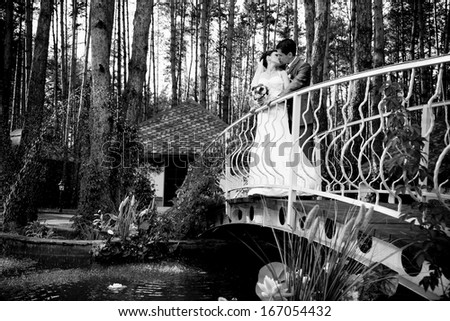 Black and white photo of just married couple hugging on old metal bridge
