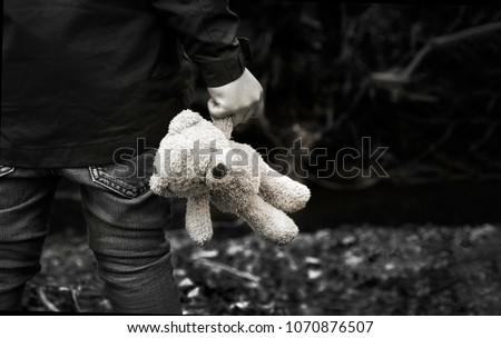 Stock Photo Black and white photo of Kid holding teddy waking alone in the forest, Rear view of a Boy standing alone holding his ted, Spoiled child, lost children or homeless kid concept