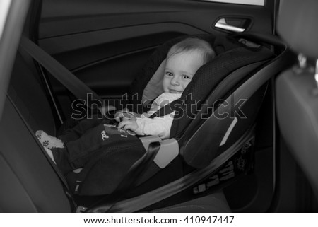 Black and white photo of little baby on back seat #410947447