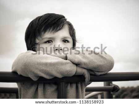 Black and white photo of lonely child standing alone in playground,Sad boy playing alone at the park,Poor kid with thinking face looking out waiting for some one at play area