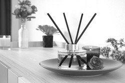 black and white photo of luxury aromatic scent reed diffuser glass bottle is used as room freshener on the wooden table in bedroom to create romantic and relax ambient with background of the flowers