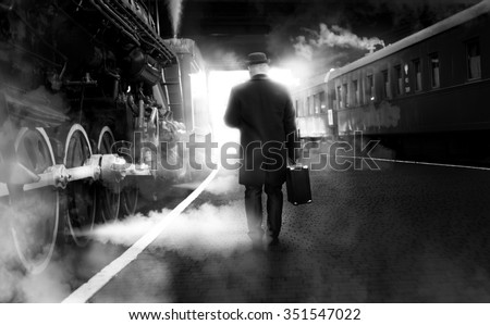 Black and white photo of man in vintage clothes walking on old railway station