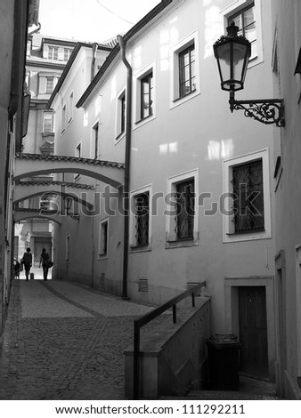 Black and white photo of narrow street with delicate lantern on the wall and reflections from windows on the opposite wall, Prague, Czech Republic