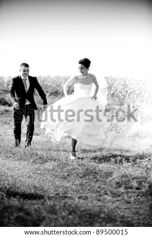 Black and white photo of newly married couple chasing in field