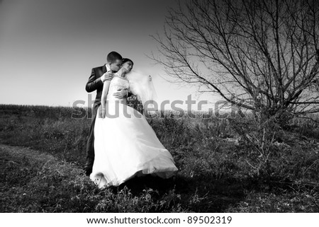 black and white photo of newly married couple hugging in field