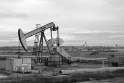 black and white photo of oil derrick with cloudy sky