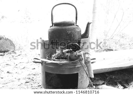 Black and white photo of old black kettle on charcoal stove #1146810716