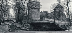 Black and white photo of old medieval castle and old stone stairs in city park in Cesis, Latvia. Cesis Castle is one of the most iconic and best preserved medieval castles in Baltics