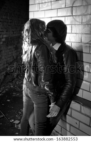 Black And White Photo Of Sexy Couple Hugging Near Brick