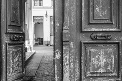 Black and white photo of shabby double door surface with peeling paint. Opened door to patio inside old house in Paris France. Vintage framed wooden door details. City life scene. Travel Europe.