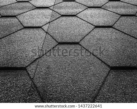 Black and white photo of soft shingles tiles closeup. The texture of the roof of the roof, made of shingles. The texture of shingles. Background on the topic of roofing construction materials.