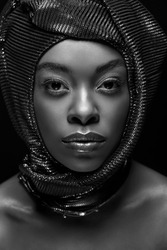 black and white photo of stylish african american woman looking at camera isolated on black