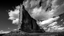 Black and White Photo of tall and fragile sandstone Rock Fin names the Tower of Babel in the desert landscape of Arches National Park near Moab in Utah, United States