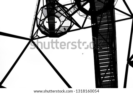 Black and white photo of the construction of Tetrahedron in german Bottrop with the staircase leading to the top of the landmark. The picture was taken from below against the sky.