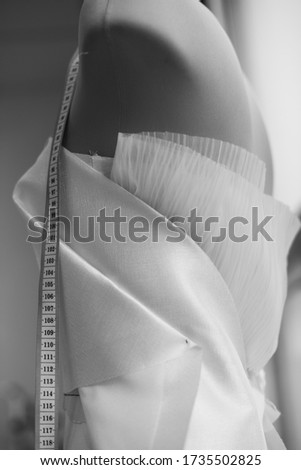Black and white photo of the elements of creating a dress, on a mannequin with a hanging centimete Stock fotó ©
