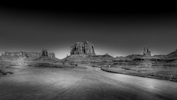Black and White Photo of The sandstone formations of West Mitten Butte, Merrick Butte and Cly Butte in the desert landscape of Monument Valley Navajo Tribal Park in southern Utah, United States
