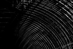 Black and white photo of tunnel framework. Arch structure. Grunge abstract background on the subject of industrial architecture.