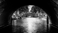 Black and White photo of View of seven historic bridges in a straight line over the Reguliersgracht, viewed from a canal boat in the Herengracht in historic Amsterdam