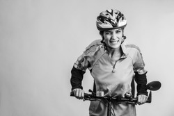 Black and white photo of woman cyclist struggling uphill on bicycle isolated on light background