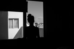 Black and white photo of woman in shadows looking trough a window staring at the city that surrounds her