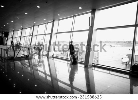 Black and white photo of woman standing in front of big panoramic window at airport