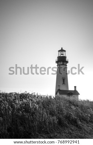 Black and white photo of Yaquina Head Lighthouse in Newport Oregon, along the Pacific Ocean coastline