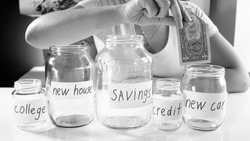 Black and white photo of young woman saving money for buying new car